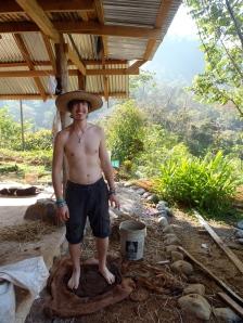 Volunteer Brian mixing cob by foot